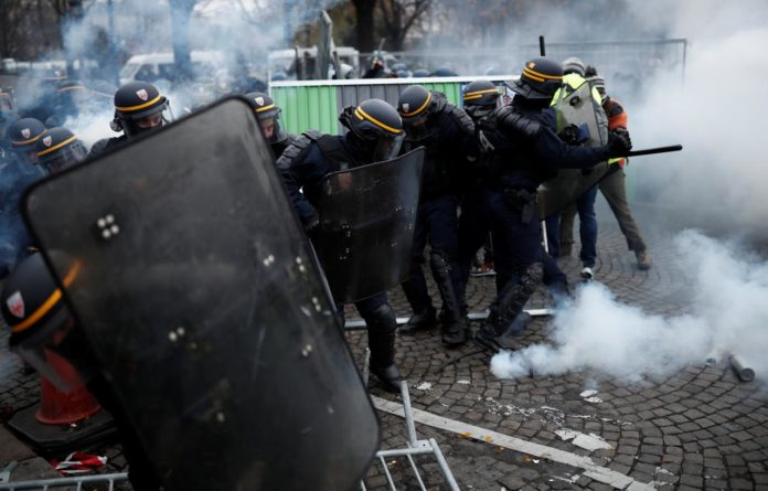 Police officers fire a tear gas during protests against higher fuel prices, on the Champs-Elysee in Paris